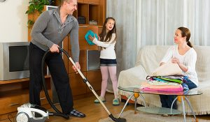 Little girl helping happy parents to clean at living room, family cleaning, mother, father, and daughter cleaning