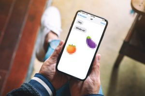 Man holding cellphone, Eggplant emoji, Peach emoji