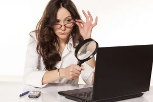 Woman holding magnifying class, woman on a laptop, woman investigating with laptop
