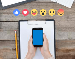 Facebook reactions, Facebook reactions on a wooden table, Group of Facebook reactions, White hand holding a cellphone, Clipboard on top of wood, Pencil on top of a wooden table