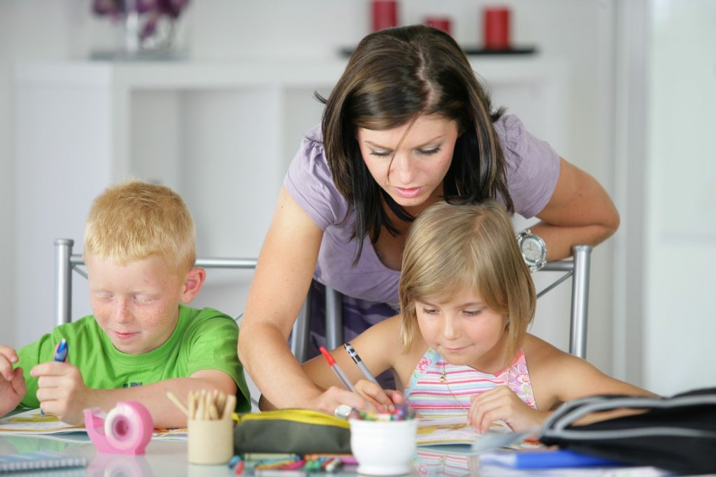 Mom teaching two kids, homeschooling, mom teaching kids