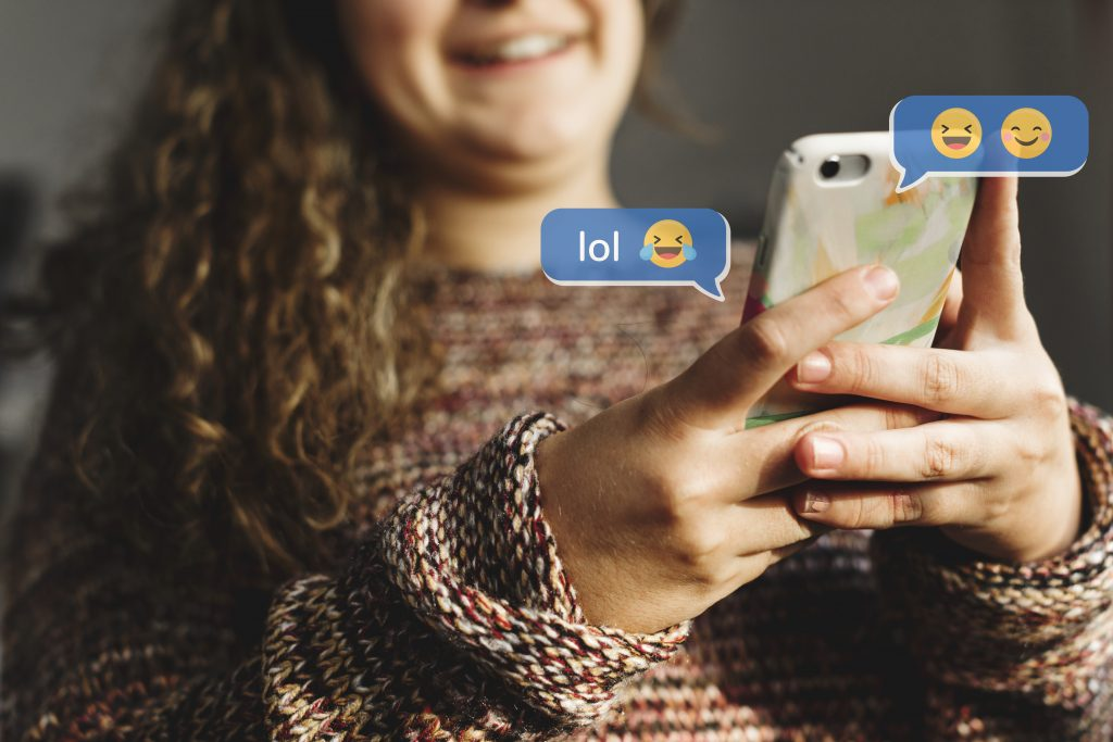 teenager using emojis on phone
