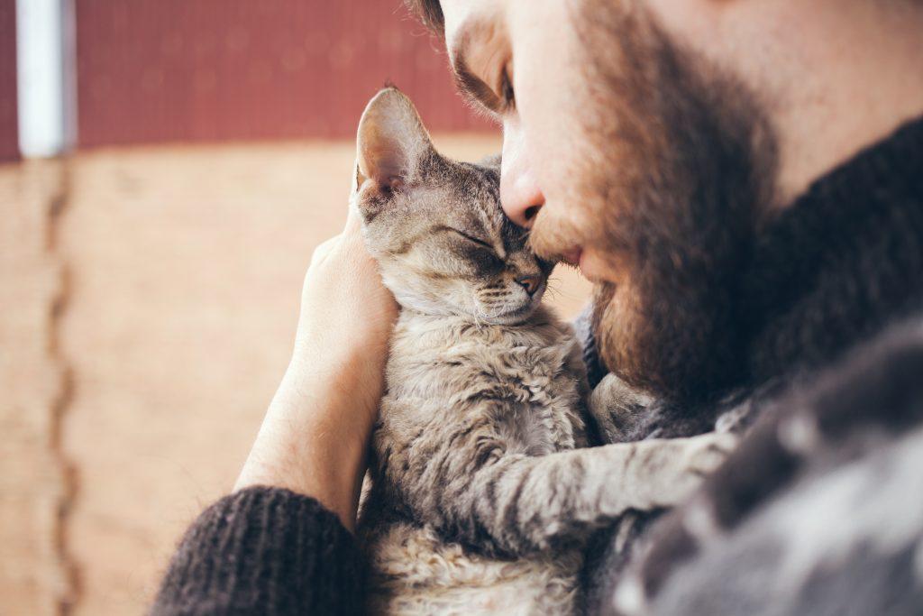 man hugging cat
