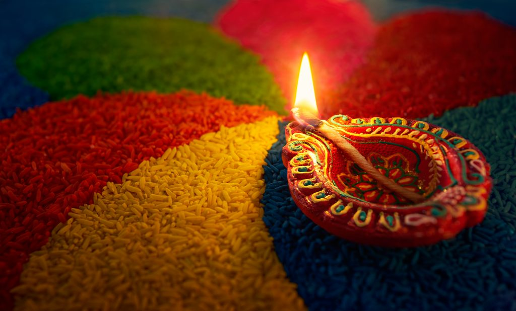 Diwali oil lamp, Diya lamp lit on colorful rangoli