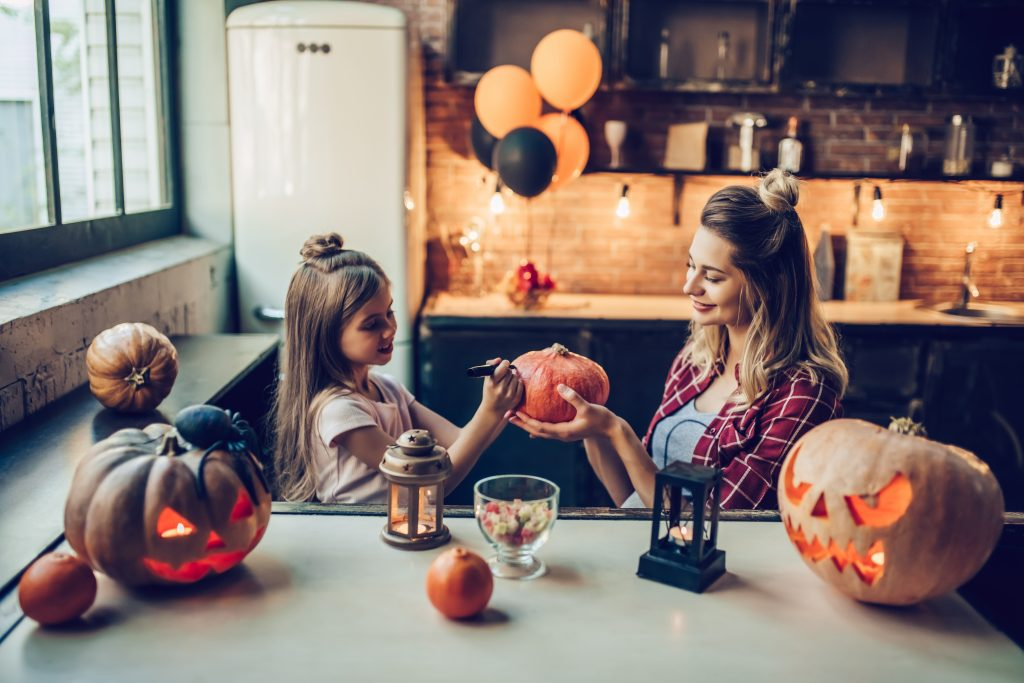 Attractive young pregnant woman with her little cute daughter are preparing to Halloween on kitchen. Mom with daughter are having fun with pumpkins while painting it.