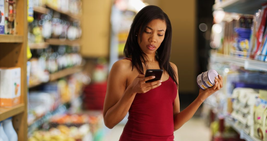 Black woman at the supermarket checking nutritional facts using app on cellphone, woman at supermarket, woman on phone