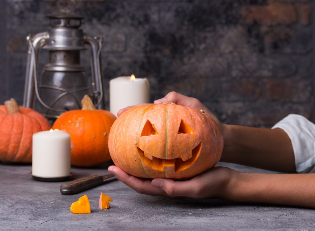 Woman carving little orange pumpkin into jack-o-lantern for Halloween holiday decoration.