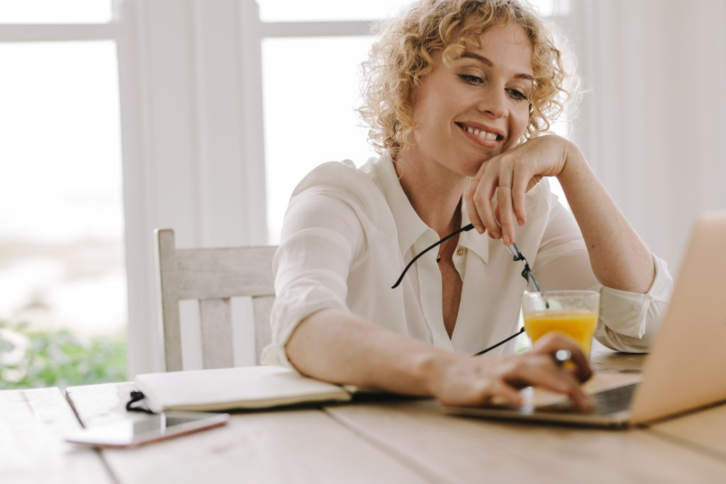 Smiling woman working from home with laptop and juice on the table. Woman using laptop holding eyeglasses in hand.