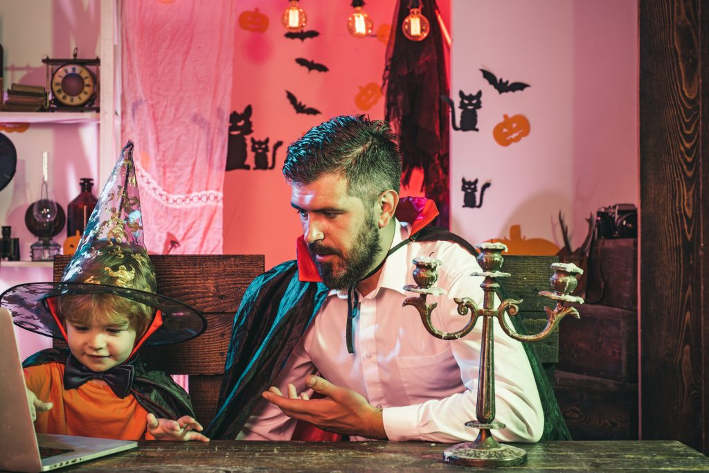 Online shopping. Holiday family concept. The father helps the child to buy goods for Halloween party on the Internet. Bearded man and boy magician are preparing for the holiday
