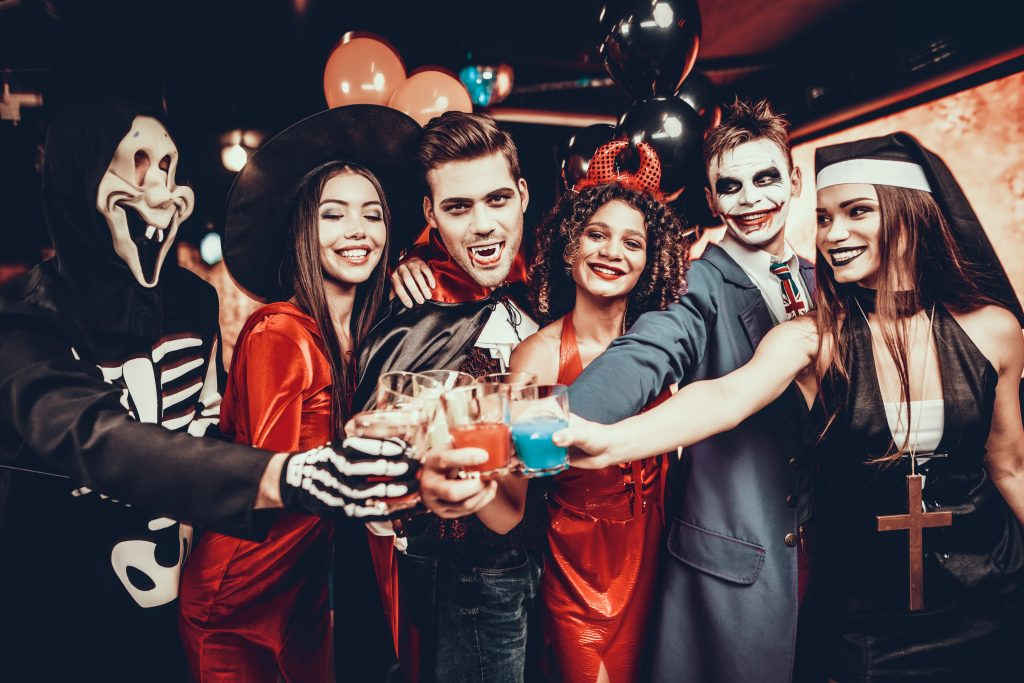 Friends in Halloween Costumes Drinking Cocktails. Group of Young Happy People Wearing Costumes at Halloween Party Drinking Cocktails and having Fun in Nightclub. Celebration of Halloween