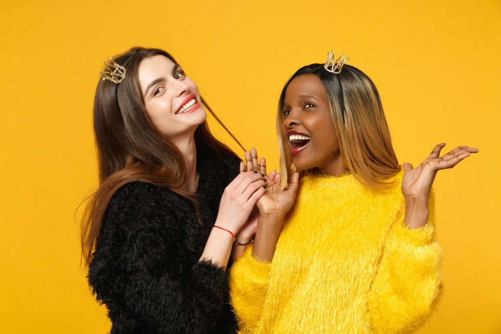 Two young women friends european and african american in black yellow clothes, best friends, friends standing, friends on a yellow background