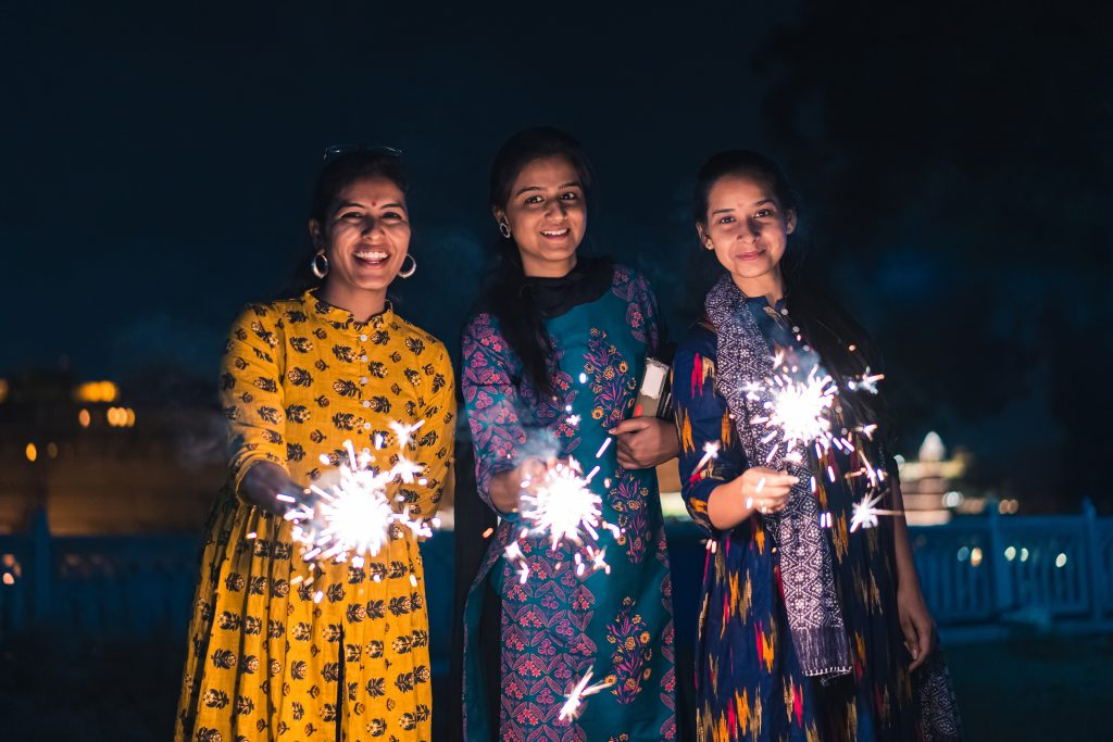 Three young Indian women holding sparklers, women holding sparklers, women holding sparklers at a Diwali festival