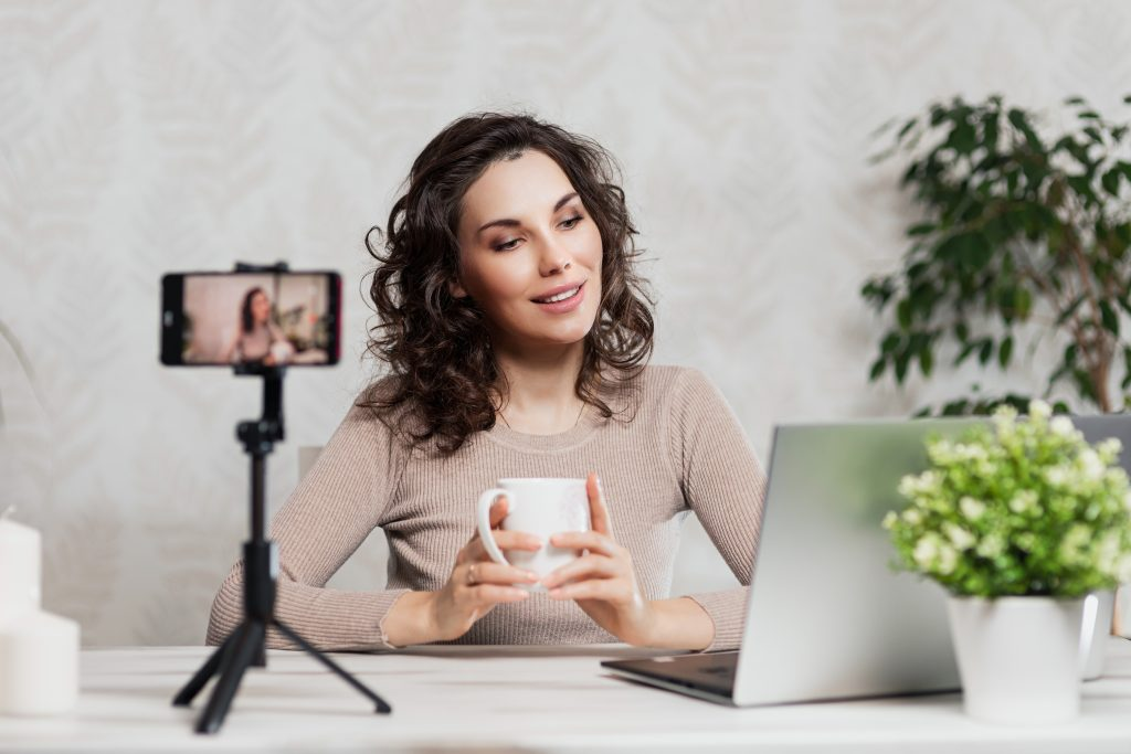 Woman staring at laptop women recording, curly-haired woman holding a cup while recording