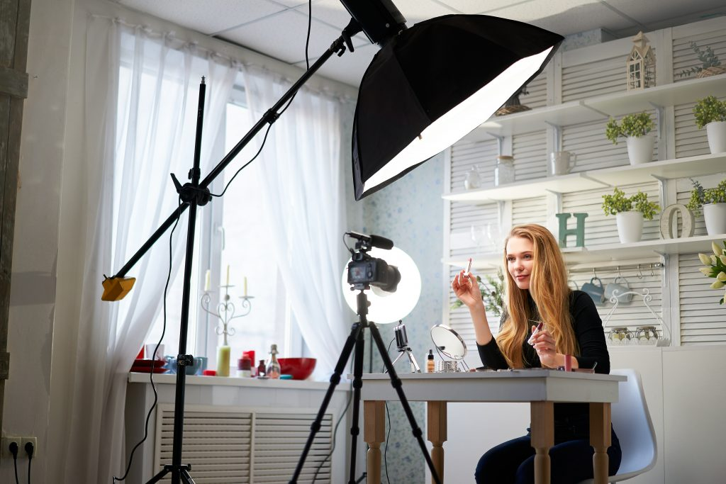 Beauty blogger woman filming daily makeup routine tutorial on camera. Influencer blonde girl live streaming cosmetics product review in home studio with professional lighting equipment. Vlogger theme.