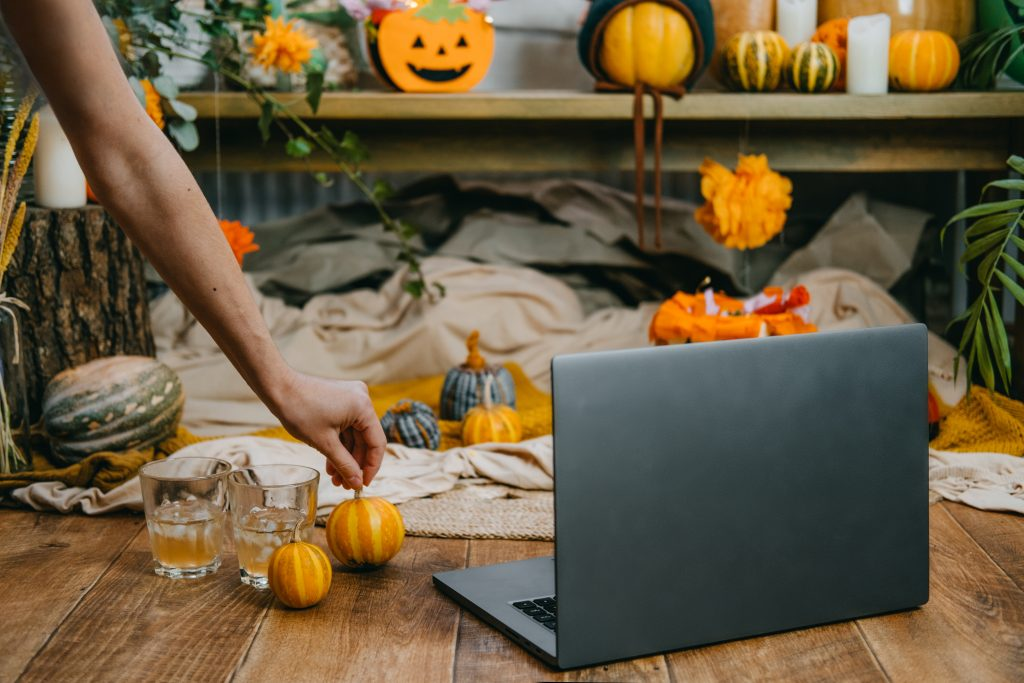 Halloween festivities in new normal, New Trick or Treating Regulations celebrate Halloween safely during COVID 19 pandemic. Open laptop ready for online meeting, pumpkins and festive decor on wooden bench.