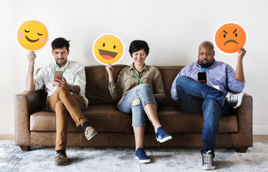 Diverse people sitting and holding emojis logos. People of different ethnicities holding emoji logos