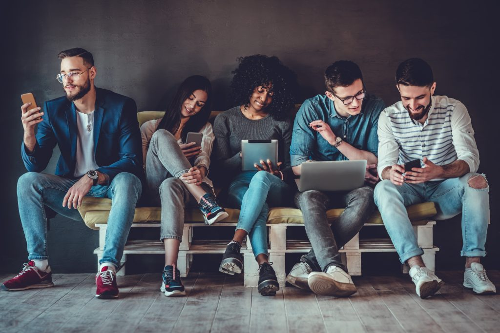 Group of happy young people sitting on sofa and using digital tablet and laptop, isolated on grey background. Best friends