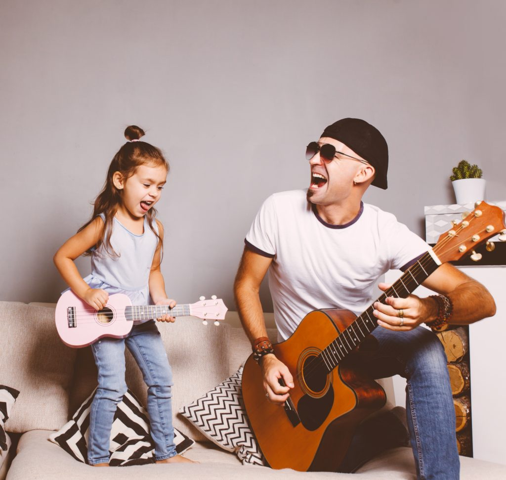 Beautiful little girl playing guitar with her father. Funny lifestyle picture. Happy family. Girl holding pink ukulele and singing and jumping,