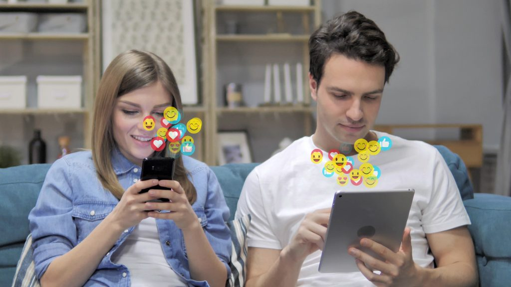 Young couple using smartphone and tablet, flying smileys, emojis and likes