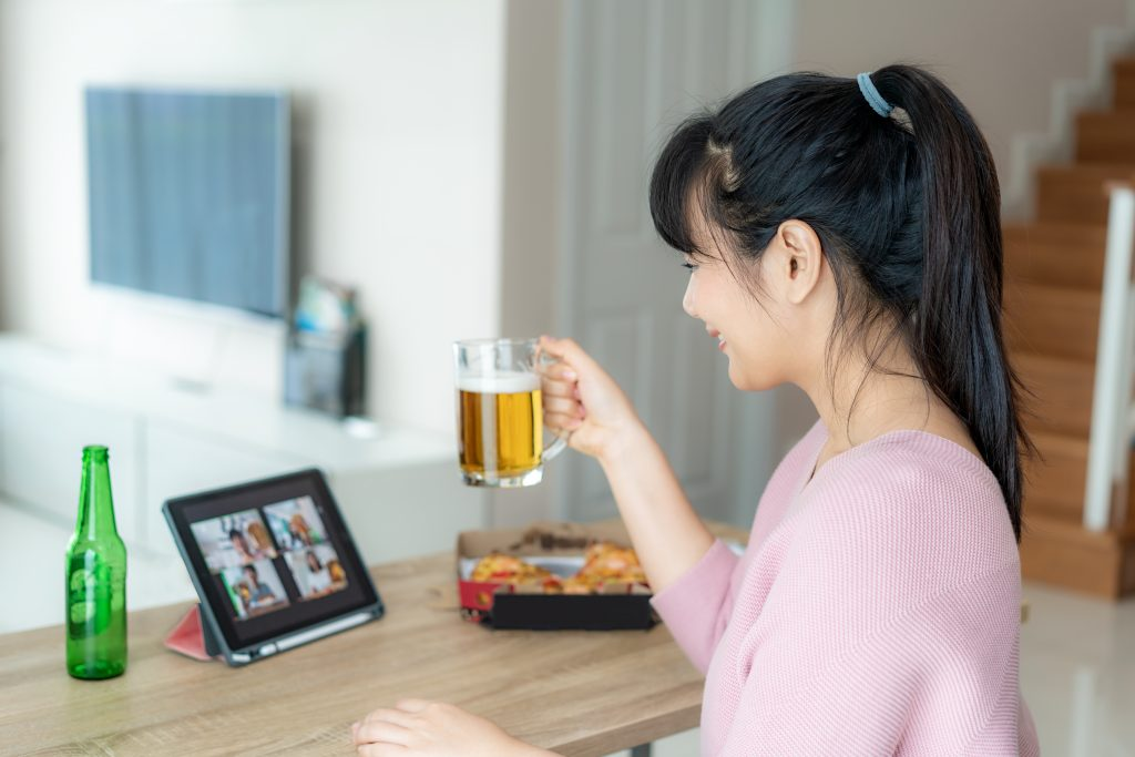 Asian woman during virtual happy hour, Asian lady at a meeting, lady drinking alcohol online together with her friend, friend talking to friend through video call