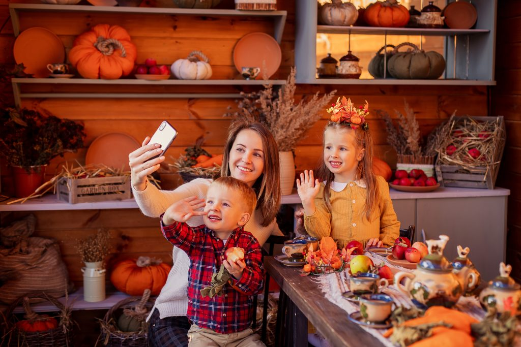 Virtual Thanksgiving dinner, mom holding phone with two kids, mom having a selfie with two kids