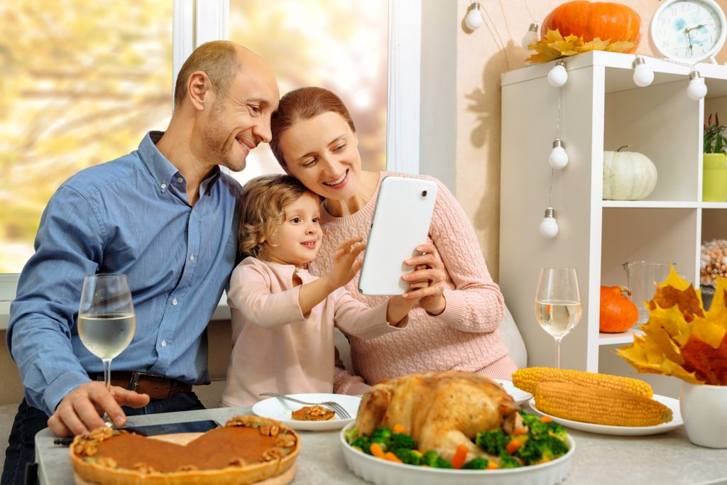A happy family have a thanksgiving dinner sending a video greeting, family on a video conference call