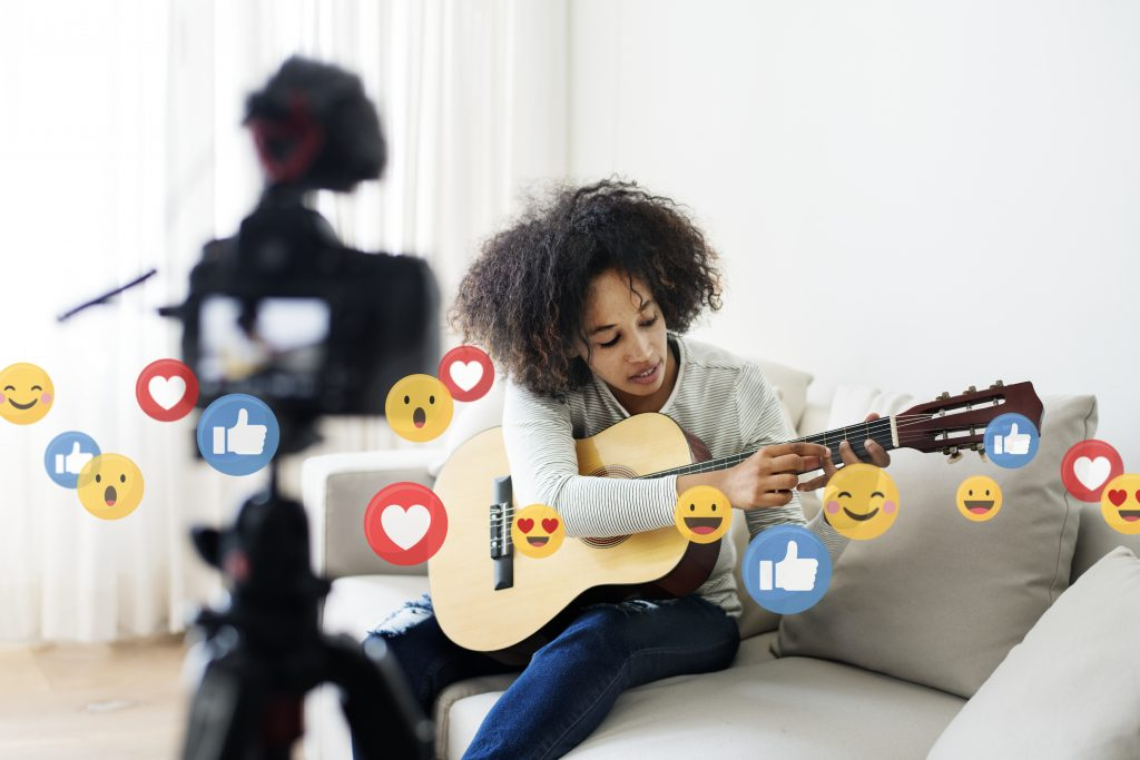 Playing guitar at home with emojis flying, flying emojis, African-American playing guitar on the couch