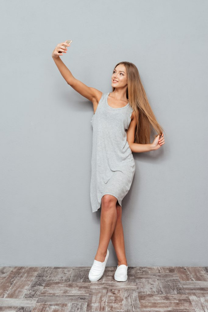 Full length portrait of a happy girl making selfie photo on smartphone on gray background, woman taking a selfie, woman in a dress taking a selfie