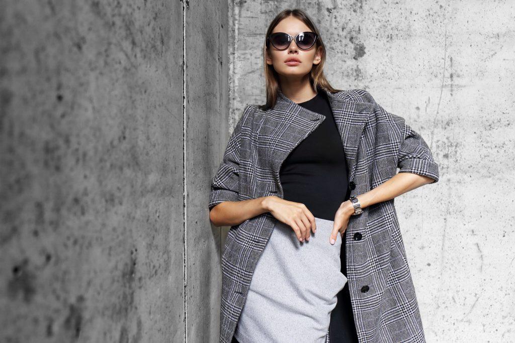 high fashion portrait of young elegant woman outdoor. Grey сoat, cat eye sunglasses, grey wall background