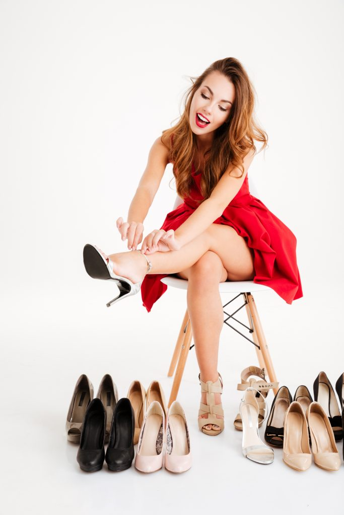 Woman in red dress trying on new high heels shoes, woman surrounded by shoes, woman trying on shoes