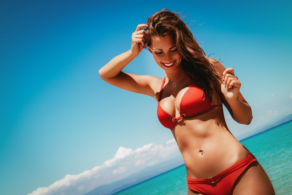 Beautiful young woman enjoying on the beach. She is posing and pensive looking down with smile on her face. Woman in a bikini. Woman in a red bikini.