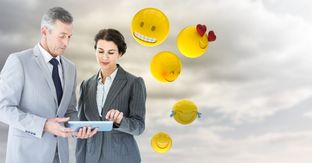 Business people with tablet against cloudy sky with emojis