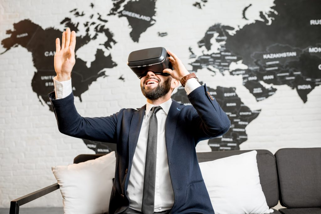 Businessman using virtual reality glasses sitting indoors with world map on the background
