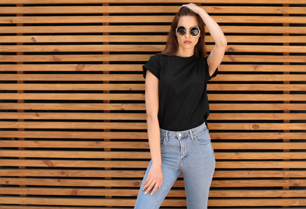 Young woman wearing black t-shirt against wooden wall on street. Urban style. Woman in a black tee. Woman holding her hair.