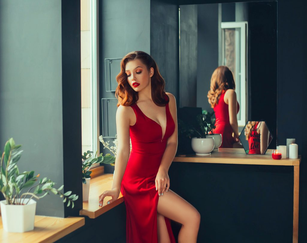 hot young adult, proud and domineering woman dressed in a long scarlet red long dress, sexually demonstrates her naked graceful leg, crouching on the window sill, room in loft stile with mirrors