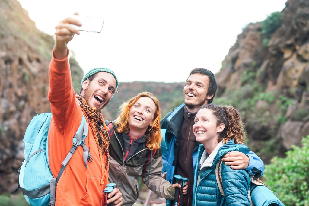 Happy friends taking a selfie on a mountain, Caucasian friends hiking,