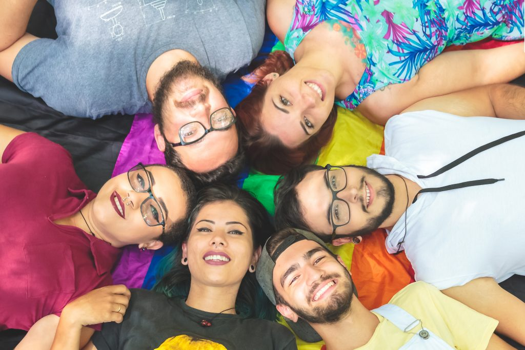 Group of lgbt couples, lgbt couples lying on a rainbow flag