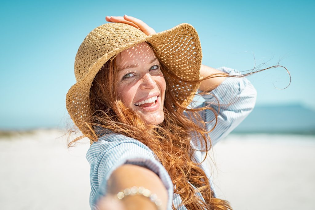 Portrait of beautiful mature woman in casual wearing straw hat in sunny warm day at seaside.Cheerful young woman smiling at beach during summer vacation. Happy girl with red hair and freckles enjoying the sun.