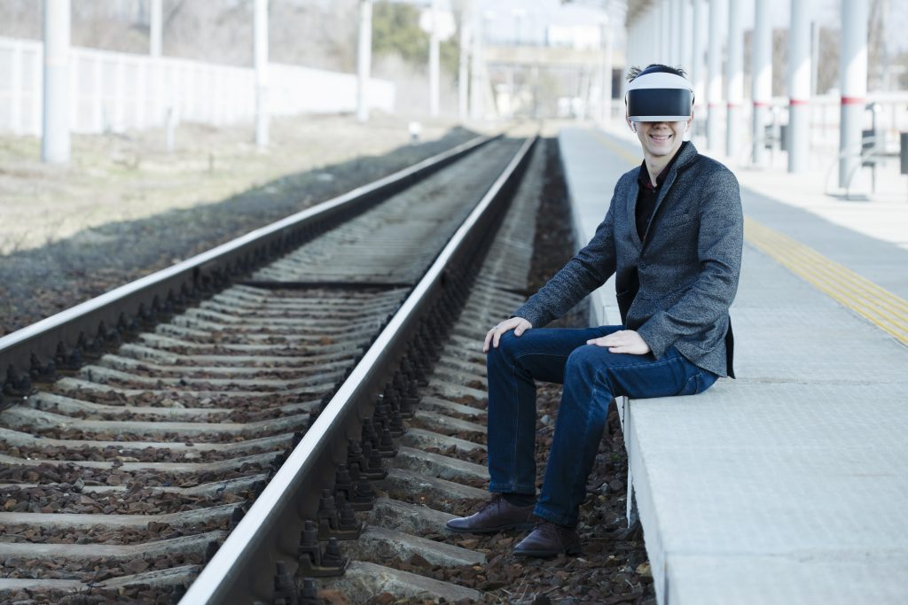 smiling young man sits near the train tracks at the station wearing virtual reality glasses. Futuristic- digital technology concept. Virtual space. Virtual reality headset and glasses