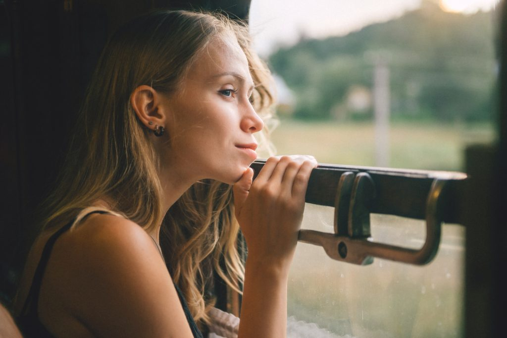 Portrait of young blonde hair girl looking out of window, teen riding moving train, teen looking out the window