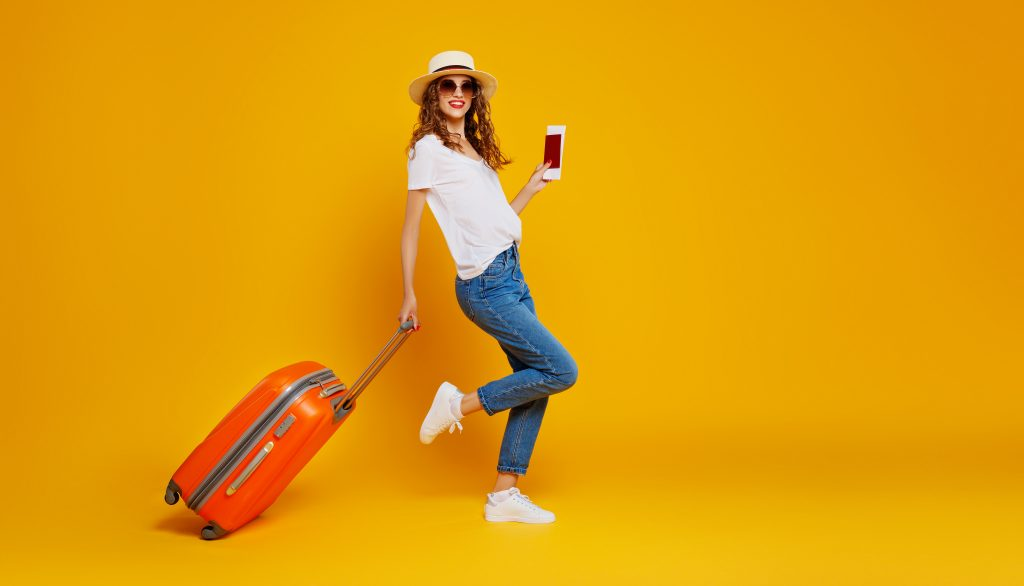 happy woman with suitcase and passport on yellow background, woman holding orange suitcase and phone in her hand