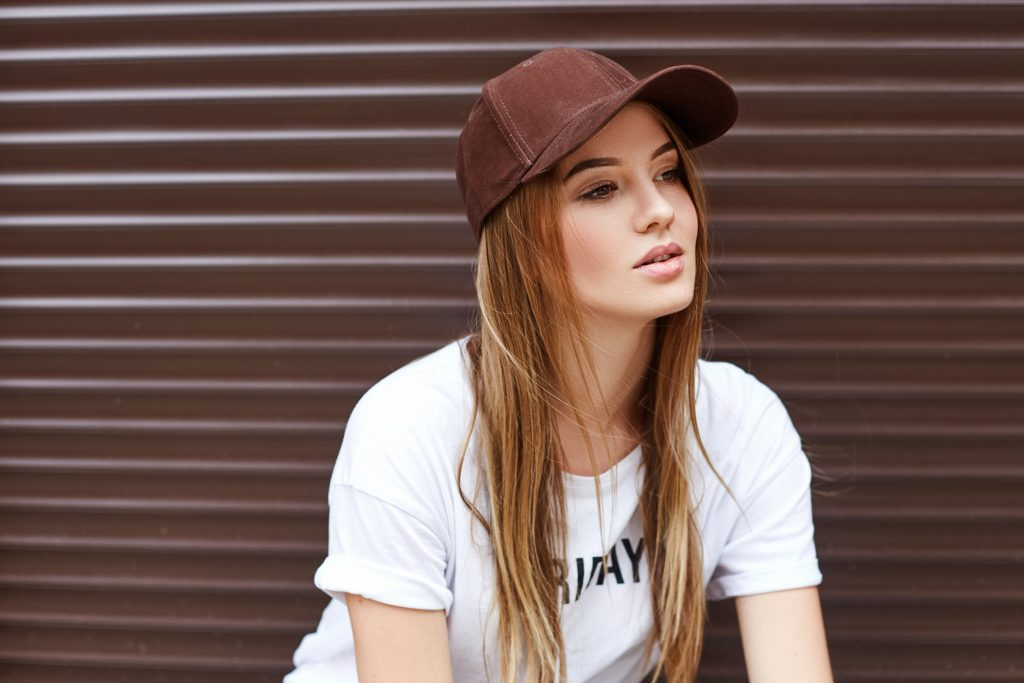 Beautiful blonde girl in a brown cap on a wall background, girl in a cap, girl wearing cap against a brown background