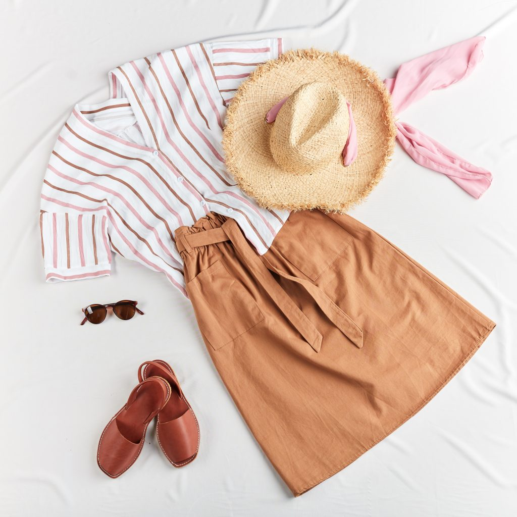 brown skirt, striped shirt, straw boater hat, leather brown sandals on white background. Overhead view of woman's casual outfit. Flat lay, top view. Trendy summer look. Flat lay of summer clothes.