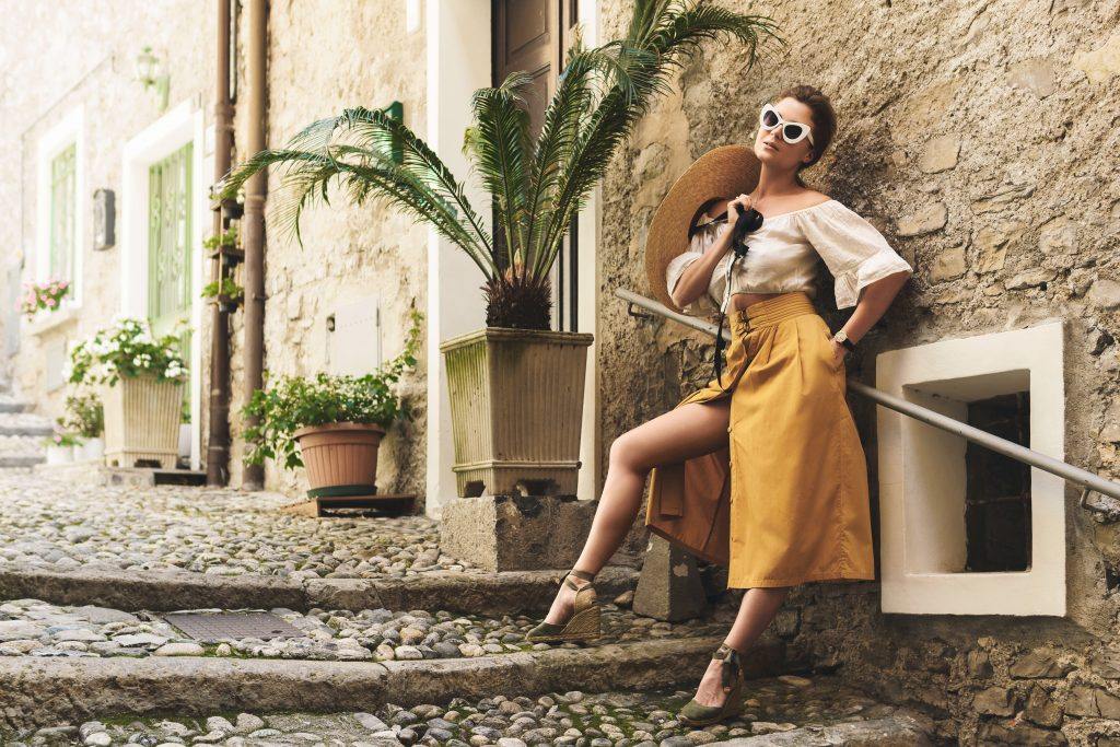 Stylish young woman posing on the streets of small Italian town, woman posing in yellow skirt, woman in shades posing