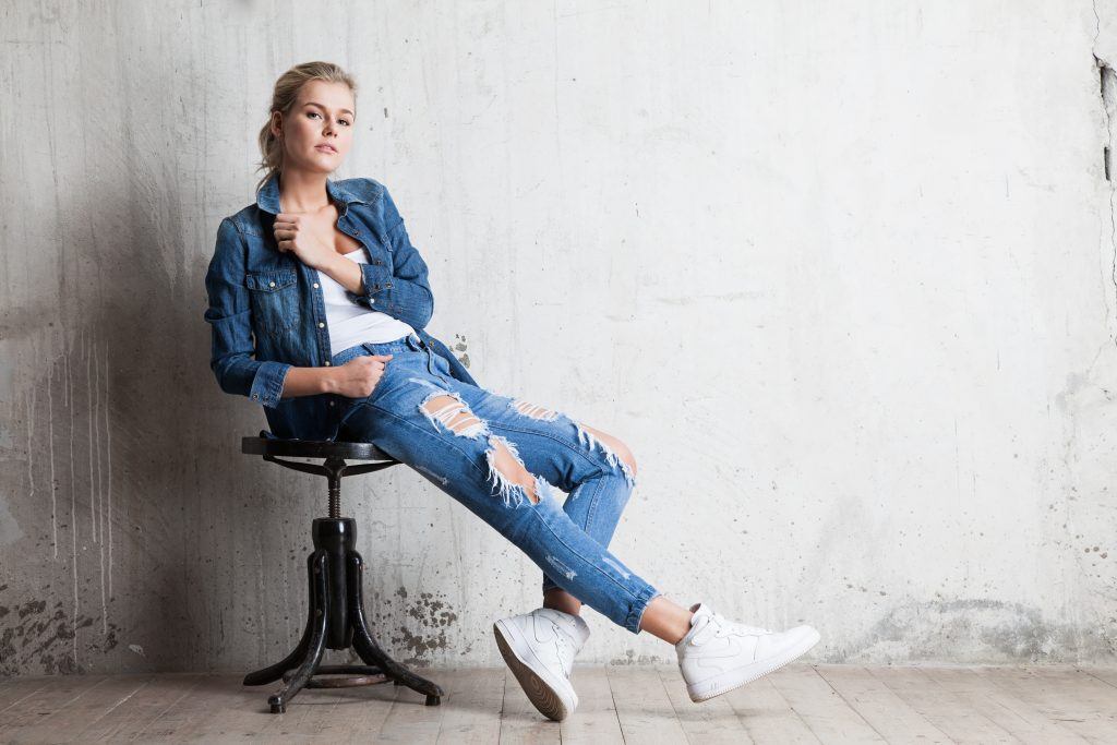 Blonde woman in ripped jeans sitting down, blonde woman in jeans and sneakers