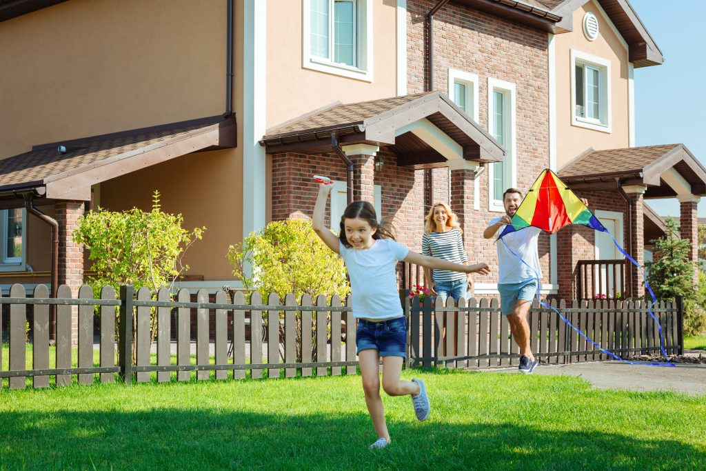 Amusing pastime. Charming little girl running across backyard of her house and flying a kite with her parents