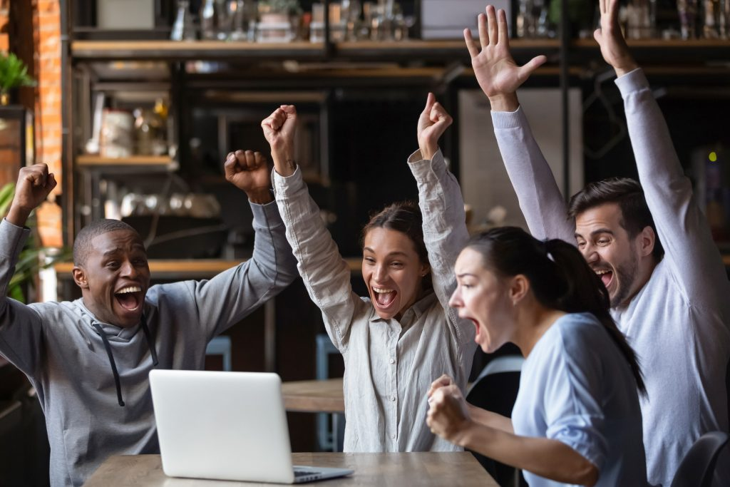 Euphoric overjoyed diverse friends screaming celebrating sport game victory goal score watching match online game on laptop sit at cafe table, happy multiracial fans supporters cheering winning team