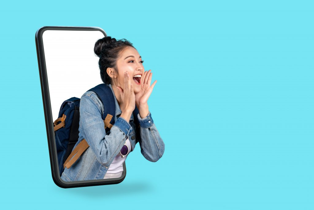 Smartphone pop up for advertising, asian woman travel backpacker shouting open mouth through from screen mobile.Girl looking to aside copy space for present promotions.Digital marketing online concept.