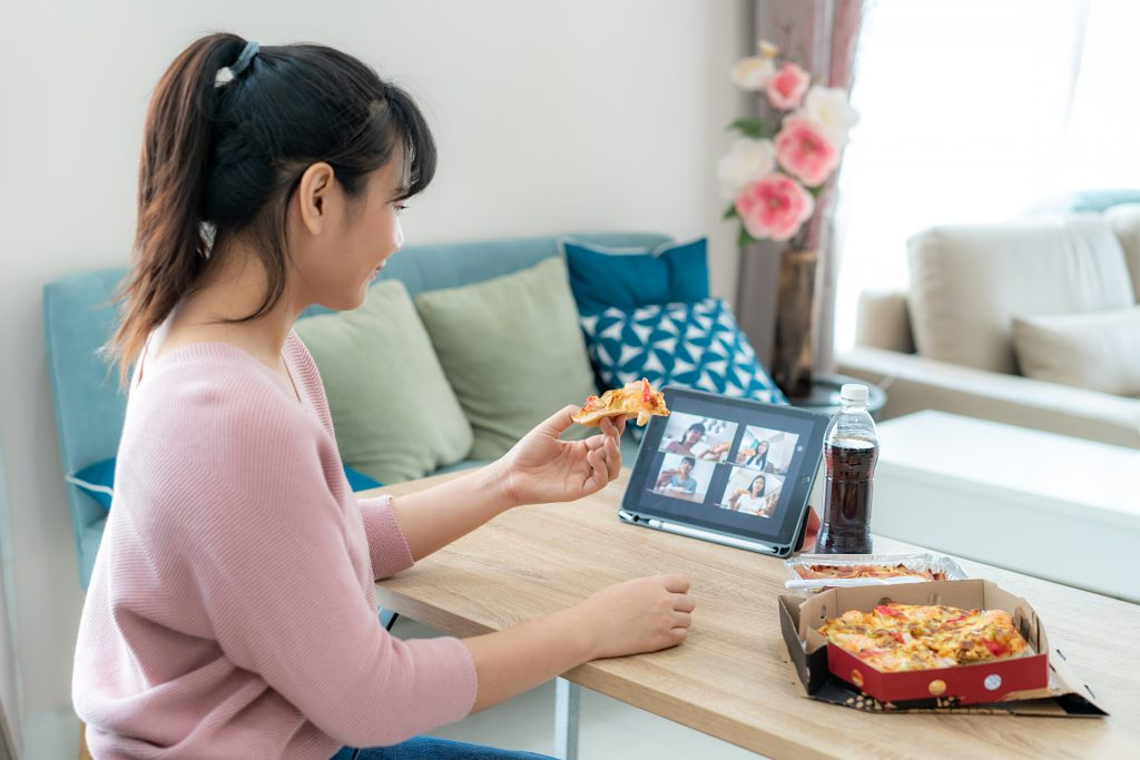 Asian woman virtual happy hour meeting party and eating food online together with her friend in video conference with digital tablet for a online meeting in video call for social distancing for infection risk.