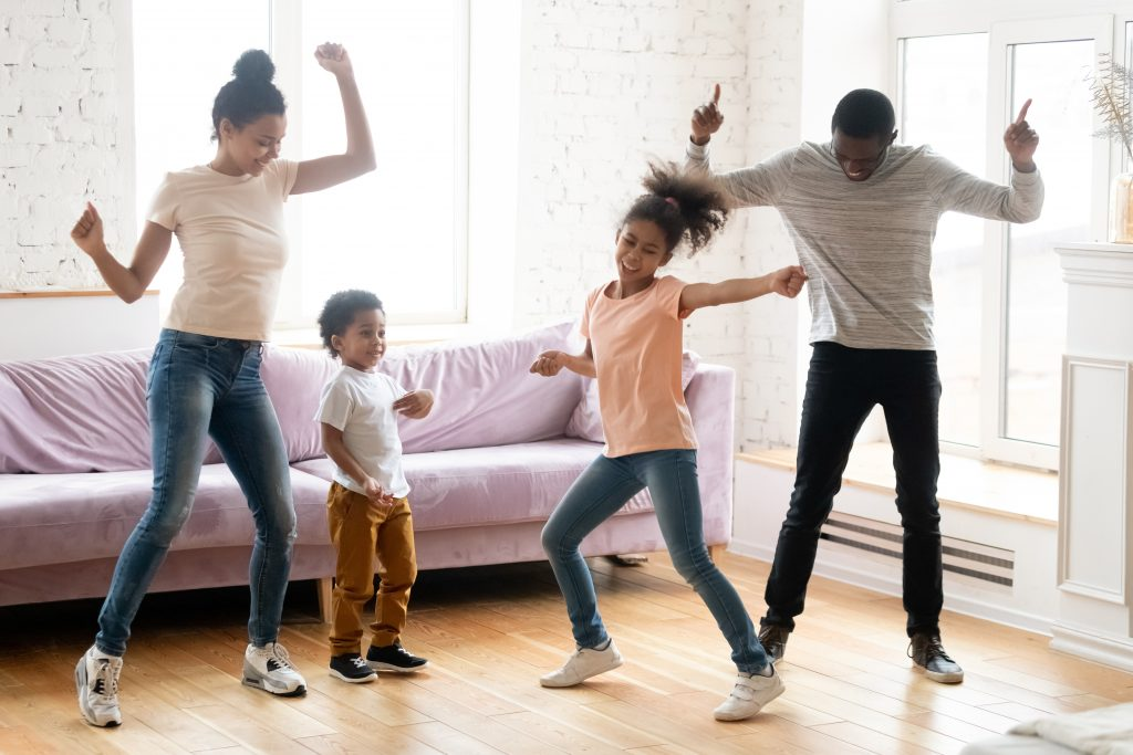 Dancing indoors. Happy black millennial parents and two children daughter and son enjoying dances in living room, active african family dad, mom and kids handle stress of being at home on quarantine